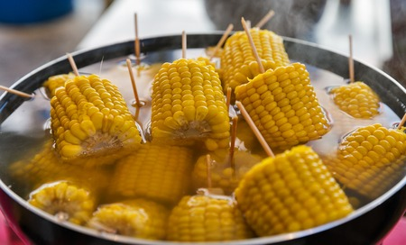 Saucepan with corn cobs boiling on stove 写真素材