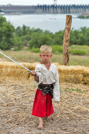 KHORTYTSIA, UKRAINE - JULY 03, 2018: Young boy Ukrainian Cossack with saber in Zaporozhian Sich. It was inhabited by Cossacks who lived beyond the rapids of the Dnieper River in the 15th-18th century. 報道画像