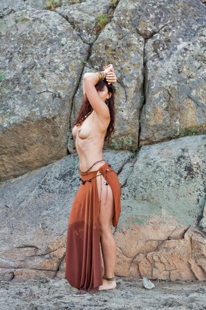 young caucasian beautiful naked Amazon woman stands in front of rocks on sand beach.