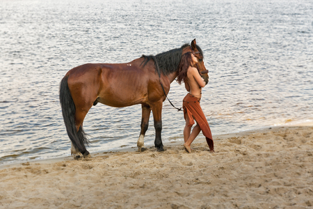 young caucasian beautiful naked Amazon woman on the river shore with red horse. Stok Fotoğraf