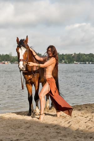 young caucasian beautiful Amazon woman on the sand river beach with red horse