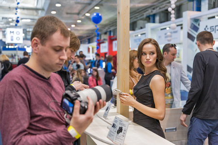 KYIV, UKRAINE - APRIL 06, 2019: People testing professional photographic cameras on Sony company booth during CEE 2019, the largest consumer electronics trade show of Ukraine in Tetra Pack EC. Banco de Imagens - 124912532