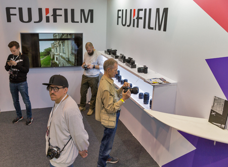 KYIV, UKRAINE - APRIL 06, 2019: People testing professional photographic cameras on FujiFilm company booth during CEE 2019, the largest consumer electronics trade show of Ukraine in Tetra Pack EC. Editorial