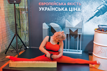 KYIV, UKRAINE - APRIL 06, 2019: Beautiful young woman gymnast twists the screws with a screwdriver in splits pose during CEE 2019, largest consumer electronics trade show of Ukraine in Tetra Pack EC.