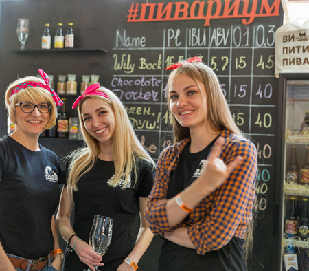 KYIV, UKRAINE - MAY 20, 2018: Young women bartenters of craft beer Pivarium brewery at Kyiv Beer Festival vol. 3 in Art Zavod Platforma. About 300 unique varieties of craft beer were presented here.