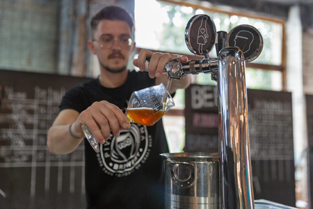 KYIV, UKRAINE - MAY 20, 2018: Bartender pours craft beer during Kyiv Beer Festival vol. 3 in Art Zavod Platforma. About 300 unique varieties of craft beer were presented here.