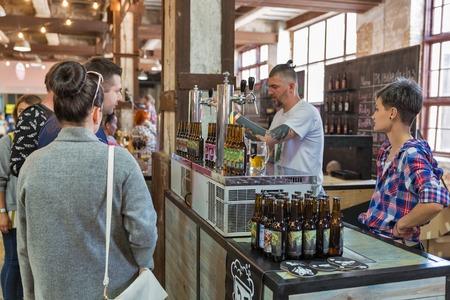KYIV, UKRAINE - MAY 20, 2018: People enjoy craft beer during Kyiv Beer Festival vol. 3 in Art Zavod Platforma. About 300 unique varieties of craft beer were presented here.