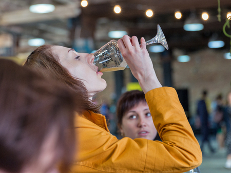 KYIV, UKRAINE - MAY 20, 2018: Young woman enjoy craft beer during Kyiv Beer Festival vol. 3 in Art Zavod Platforma. About 300 unique varieties of craft beer were presented here.