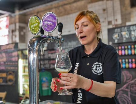KYIV, UKRAINE - MAY 20, 2018: Woman bartender pours Volynski Browar Brewery craft beer at Kyiv Beer Festival vol. 3 in Art Zavod Platforma. About 300 unique varieties of craft beer were presented here Redakční