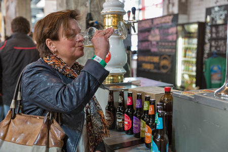 KYIV, UKRAINE - MAY 20, 2018: Woman enjoy craft beer during Kyiv Beer Festival vol. 3 in Art Zavod Platforma. About 300 unique varieties of craft beer were presented here.