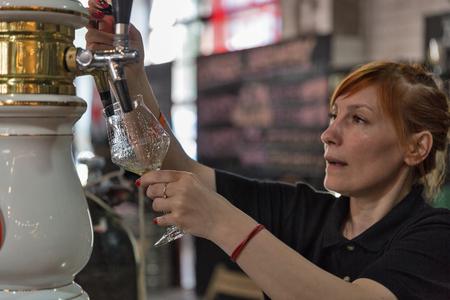 KYIV, UKRAINE - MAY 20, 2018: Woman bartender pours Volynski Browar Brewery craft beer at Kyiv Beer Festival vol. 3 in Art Zavod Platforma. About 300 unique varieties of craft beer were presented here