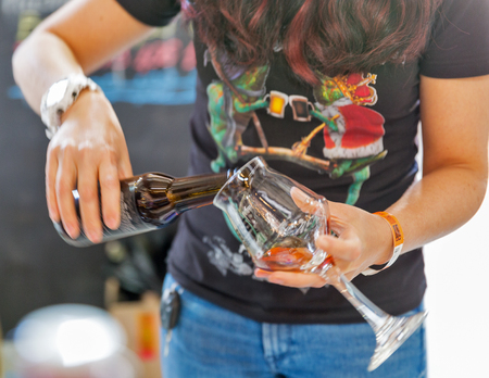 KYIV, UKRAINE - MAY 20, 2018: Woman bartender pours craft beer closeup during Kyiv Beer Festival vol. 3 in Art Zavod Platforma. About 300 unique varieties of craft beer were presented here.