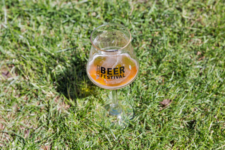 KYIV, UKRAINE - MAY 20, 2018: Glass of craft beer with festival logo closeup during Kyiv Beer Festival vol. 3 in Art Zavod Platforma. About 300 unique varieties of craft beer were presented here.