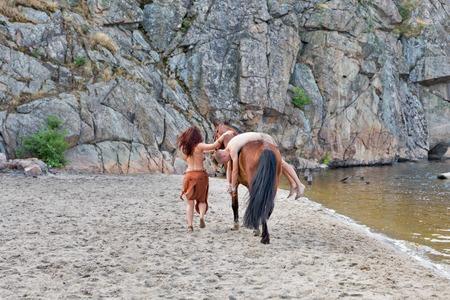 joven blanco en taparrabos tomado cautivo por la joven y bella mujer caucásica Amazona en caballo rojo. La arena de la playa del río con la montaña en segundo plano.