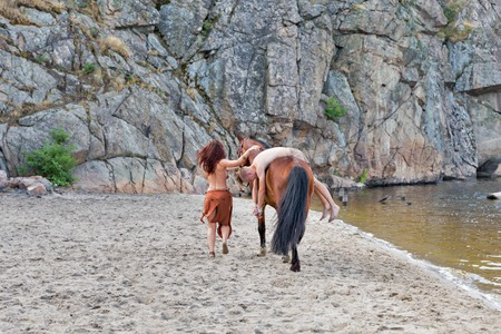 young white man in loincloth taken captive by the young caucasian beautiful naked Amazon woman on red horse. the sand river beach with mountain in background