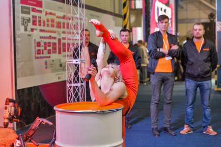KYIV, UKRAINE - APRIL 06, 2019: Beautiful young woman gymnast performance with electric screwdriver at Dnipro-M booth during CEE 2019, largest consumer electronics trade show in Tetra Pack EC.