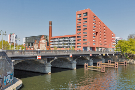 BERLIN, GERMANY - APRIL 18, 2019: People walk along An der Schilling bridge over Spree river. Radialsystem V cultural and event center, European Bible Training Center and Hotel Ibis in the background.