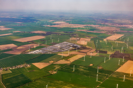 Aerial view over landscape with wind mill turbine farm and huge car parking lot close to Berlin, Germany. Banco de Imagens