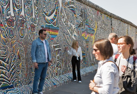 BERLIN, GERMANY - APRIL 18, 2019: People visit Wall barrier and East Side Gallery, international memorial for freedom along Spree river at sunny day.