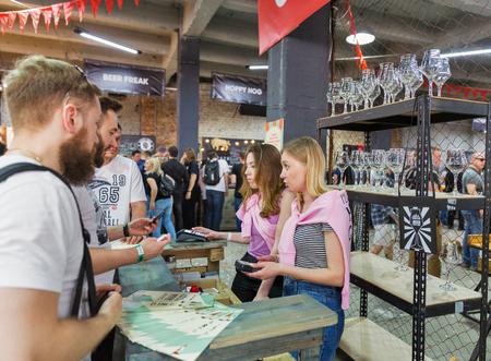 KYIV, UKRAINE - MAY 18, 2019: People visit beer glasses booth during Kyiv Beer Festival vol. 4 in Art Zavod Platforma. More than 60 craft beer breweries were presented here.