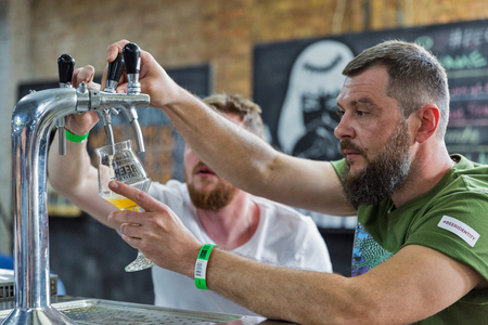 KYIV, UKRAINE - MAY 18, 2019: Bartenders pour craft beer at Kyiv Beer Festival vol. 4 in Art Zavod Platforma. More than 60 craft beer breweries were presented here.
