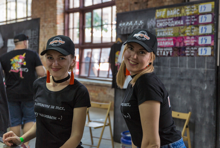 KYIV, UKRAINE - MAY 18, 2019: Bartenders work at Happy-Hop brewery booth during Kyiv Beer Festival vol. 4 in Art Zavod Platforma. More than 60 craft beer breweries were presented here.