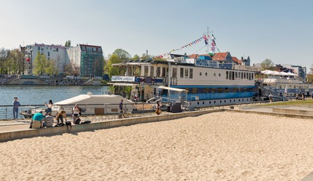 BERLIN, GERMANY - APRIL 19, 2019: People walk along floating Eastern Western Comfort Hostelboat on Spree river. Berlin is the capital and largest city of Germany by both area and population.