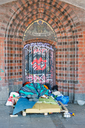 BERLIN, GERMANY - APRIL 18, 2019: A homeless man asleep over a blanketon with the dog on the ground in a Oberbaum bridge. Berlin is the capital and largest city of Germany by both area and population.
