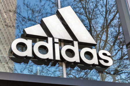 BERLIN, GERMANY - APRIL 18, 2019: Adidas store with logo sign visible outside. It is a multinational corporation that designs and manufactures sport shoes, clothing and accessories. Редакционное