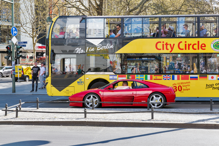 BERLIN, GERMANY - APRIL 18, 2019: Tourists visit Kurfurstendamm street on Hop On Hop Off City Sightseeing Tour bus. Berlin is the capital and largest city of Germany by both area and population.