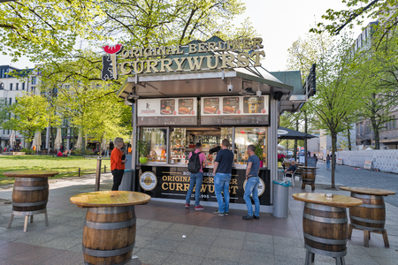 BERLIN, GERMANY - APRIL 18, 2019: People visit Original Berliner Currywurst, curry sausage fast food outdoor cafe on Wittenberg square. Berlin is the capital and largest city of Germany.
