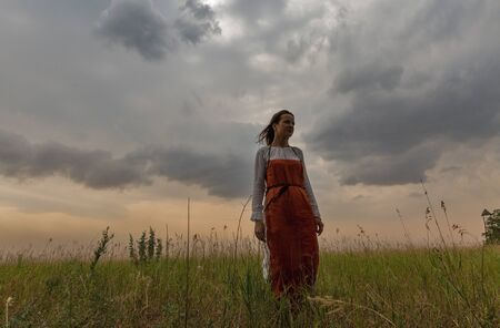 KHORTYTSIA, UKRAINE - JULY 03, 2018: Middle aged white woman in medieval dress walks in the steppe with thunder sky summer landscape on Khortytsia island. Banco de Imagens - 124913286