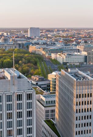Aerial cityscape with Tiergarten park and Reichstag building at sunset close to Potsdamer Square in Berlin, Germany.