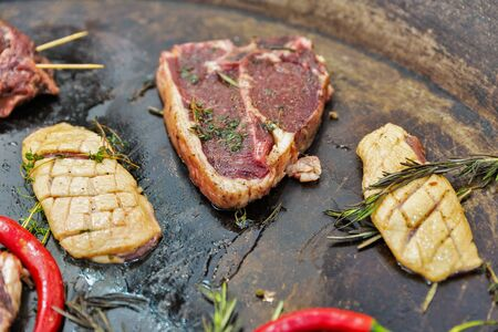 Cooking grill beef steak on rib-in bone and duck breast with rosemary and thyme closeup