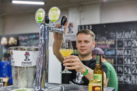 KYIV, UKRAINE - MAY 18, 2019: Bartender of Friday craft brewery works at Kyiv Beer Festival vol. 4 in Art Zavod Platforma. More than 60 craft beer breweries were presented here.
