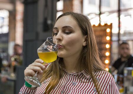 KYIV, UKRAINE - MAY 18, 2019: Young beautiful woman drink craft beer closeup during Kyiv Beer Festival vol. 4 in Art Zavod Platforma. More than 60 craft beer breweries were presented here.