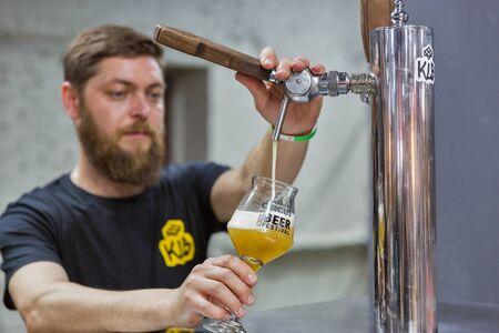 KYIV, UKRAINE - MAY 18, 2019: Bartender pours KLB craft beer at Kyiv Beer Festival vol. 4 in Art Zavod Platforma. More than 60 craft beer breweries were presented here.