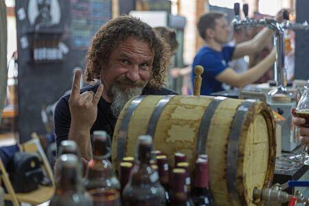 KYIV, UKRAINE - MAY 18, 2019: Man bartender works at Kyiv Beer Festival vol. 4 in Art Zavod Platforma. More than 60 craft beer breweries were presented here. Redakční