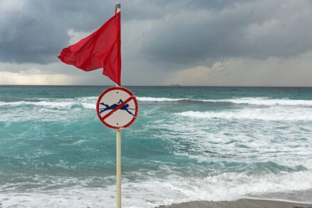 Red warning flag with no swimming symbol on sea beach Фото со стока