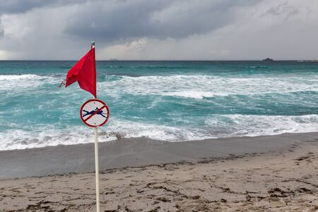 Red warning flag with no swimming symbol on sea beach Stock fotó