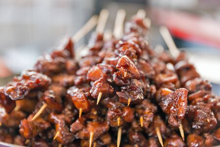 Delicious appetizing skewers of meat pieces in sweet and sour sauce, strung on wooden sticks closeup.