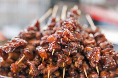 Köstliche appetitliche Spieße von Fleischstücken in süß-saurer Soße, aufgereiht auf Holzstäbchen, Nahaufnahme.