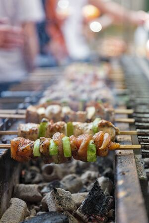 Appetizing shashlik with turkey meat and zucchini roasted on skewers, closeup outdoors. Street food. Фото со стока