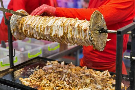 Cooking shawarma, meat layers strung on a skewer, chopped meat is on grill surface, outdoors
