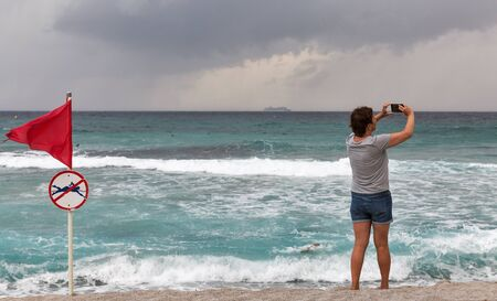 Woman makes stormy smart phote photo. Red warning flag with no swimming symbol on sea beach Stock fotó