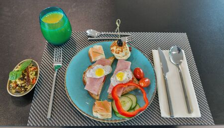 Breakfast with ham sandwiches, smoked salmon, bread, vegetables, bulgur rice salad and orange juice served in small family hotel on tablecloth closeup