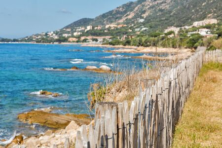 Stunning Corsica coastline with wooden fence, rocky beach and tourquise clear water near Ajaccio, Corsica, France. Stok Fotoğraf
