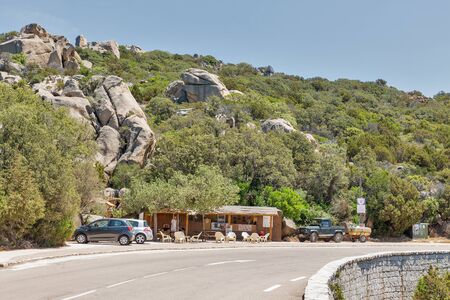 ROCCAPINA, CORSICA, FRANCE - JULY 17, 2019: People visit small roadside cafe on Roccapina coast. Corsica is located southeast of the French mainland and west of the Italian Peninsula.