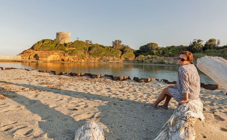 White middle age tanned woman enjoys sunset on Corsiaca island sand beach, France. Diana Genoese tower in the background beside the sea. Imagens