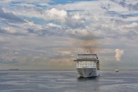 Luxury cruise ship sailing in the open sea with dramatic clouds. Livorno, Italy. 스톡 콘텐츠